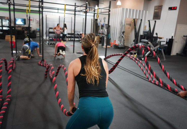 woman in the gym using battle ropes